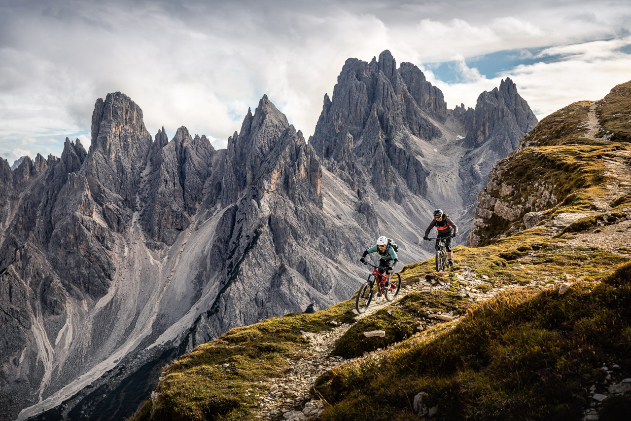 Mountainbikers riding down exposed trail in front of mountain range Cadini di Misurina, near Auronzo di Cadore, Italy, Veneto, Dolomites