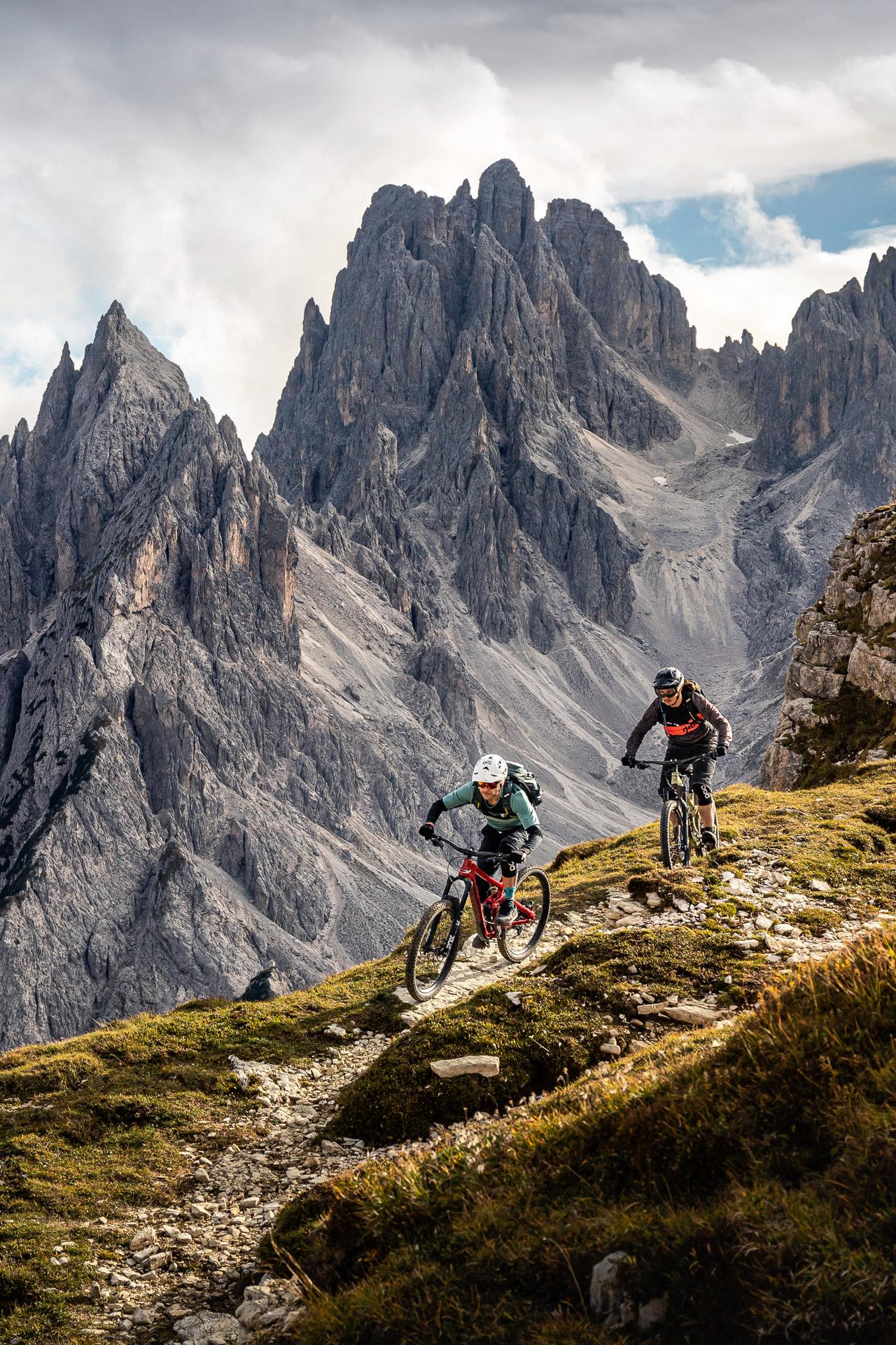 Mountainbikers riding down exposed trail in front of mountain range Cadini di Misurina, near Auronzo di Cadore, Italy, Veneto, Dolomites